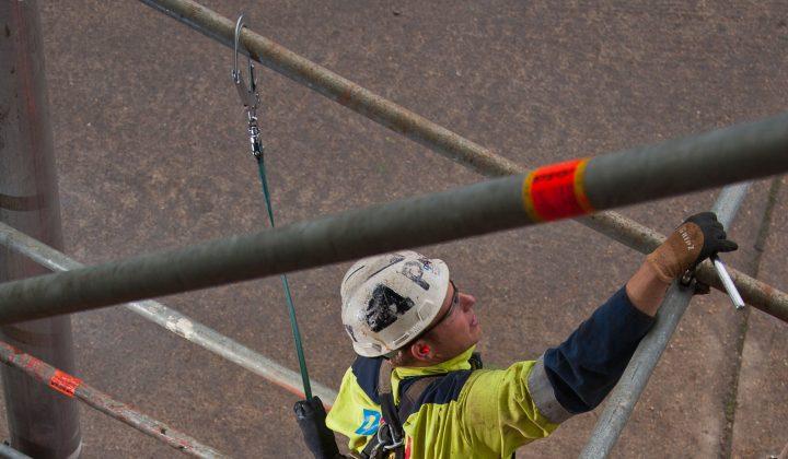 Bauarbeiter mit Fallsicherung auf einem Gerüst
